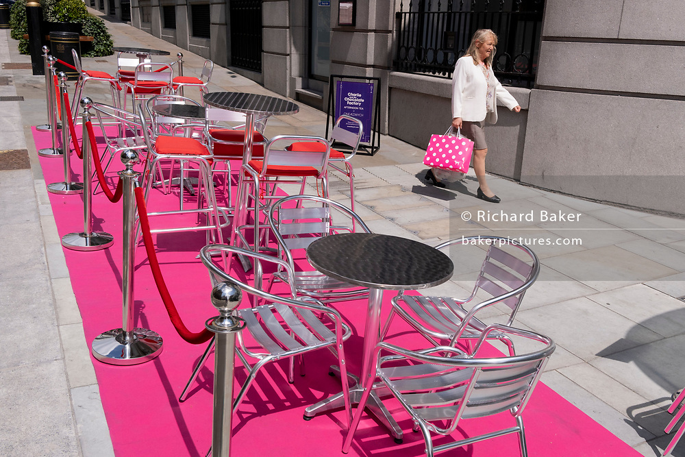 A woman carries a pink shopping bag past a pink carpet with silver street tables and seating which stretches uphill in Aldwych, on 23rd June 2021, in Westminster, London, England.