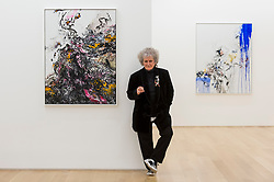 """© Licensed to London News Pictures. 14/10/2020. LONDON, UK. Artist Maggi Hambling poses with her works """"Covid Spring, 2020 (L) and """"Self portrait, working"""", 2020, at the preview of Maggi Hambling: 2020 at Malborough Gallery in Mayfair.  The exhibition of recent paintings coincides with Hambling's 75th Birthday and runs 15 October to 21 November 2020.  Photo credit: Stephen Chung/LNP"""