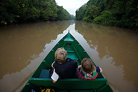 Kids ride in a boat up the Menangul River, Borneo.