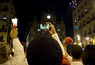 A reveller takes a photo while others raise red scarves and candles as they sing 'Pobre de Mi' during the end of the San Fermin Festival on July 15, 2014, in Pamplona, Basque Country. Every year, tens of thousands of people pack Pamplona's streets for a drunken kick-off to one os worls's best-known fiesta: the nine-day San Fermin bull-running festival. (Ander Gillenea / Bostok Photo)