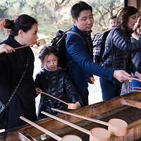 Locals and tourists washing their hands before entering the Meiji Shrine in the Shibuya neighborhood of Tokyo, Japan.
