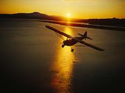 Leon Alsworth flying his Taylorcraft over Lake Clark at sunset, Lake Clark National Preserve, Alaska.