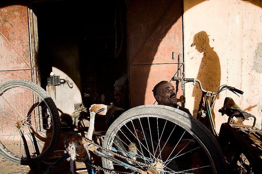 "Local bike mechanic Dligui ""Le Cycliste"" Abdelkader chats with customer Dafali Aziz as he services a bike outside his shop in the dusty one-road town of Tagounite, Morocco on November 7, 2007."