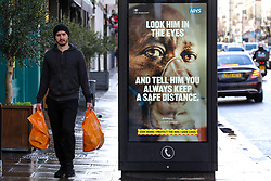 © Licensed to London News Pictures. 02/02/2021. London, UK. A shopper without wearing a protective face covering walks past the government's 'Look him in the eyes - And tell him you always keep a safe distance.' awareness publicity campaign poster in Haringey, north London. Door-to-door testing for the South Africa coronavirus variant will begin certain postcodes in the London boroughs of Merton, Haringey and Ealing to avoid the spread of the virus. Minister are telling members of the public in areas where South Africa variant has been found to 'think again' before leaving home. Photo credit: Dinendra Haria/LNP
