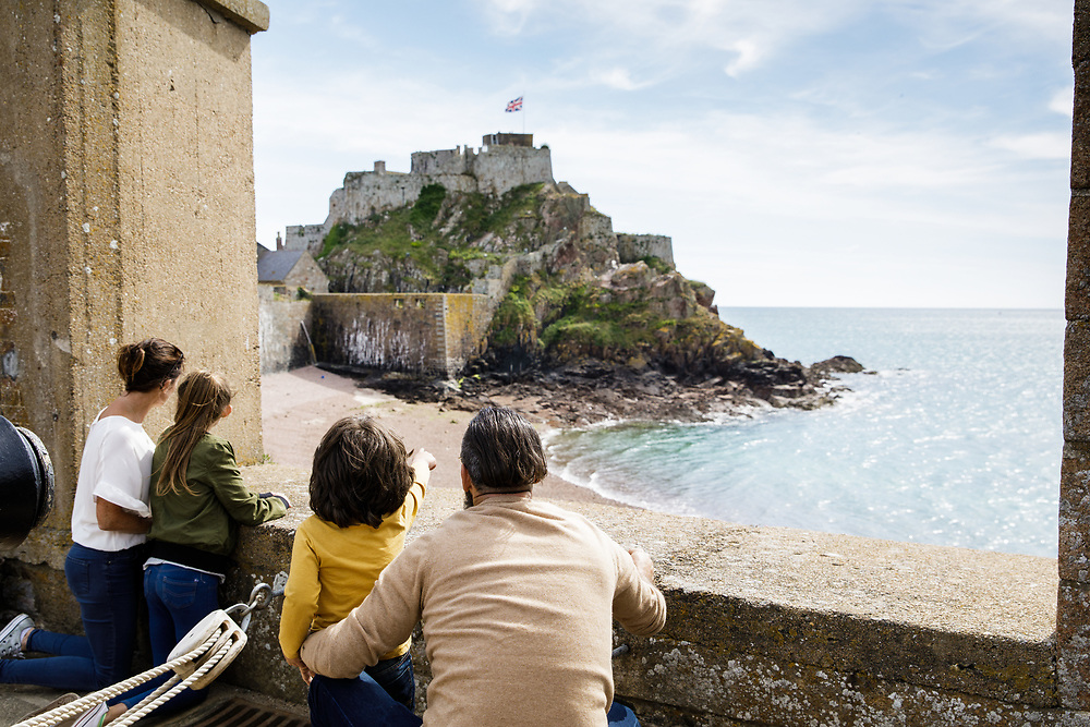 Family exploring the grounds and taking in the view at Elizabeth Castle, the historic heritage site and tourist attraction in Jersey, Channel Islands
