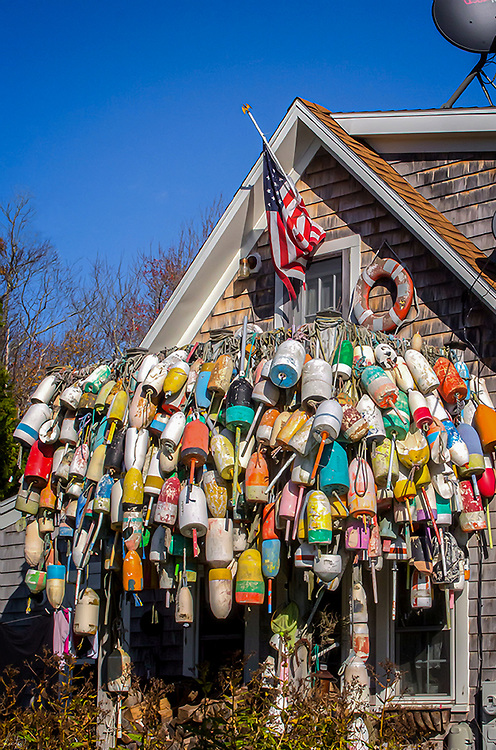 A cottage with one side literally covered with lobster trap buoys.