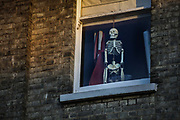 Skeleton hanging in a window of a home during the lockdown because of the COVID-19 pandemic, 7pm on 23rd April 2020 in London, United Kingdom. There is a dark humour that emerges in the difficult times of a deadly epidemic.