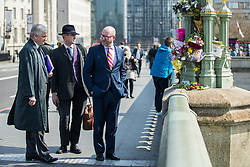 © Licensed to London News Pictures . 27/03/2017 . London , UK . PATRICK O'FLYNN , GAWAIN TOWLER and PAUL NUTTALL cross north over Westminster Bridge in London , and look at flowers and tributes fixed to fixtures outside Parliament in Westminster , left by well wishers in response to Khalid Masood's terrorist attack and the killing of PC Keith Palmer . Photo credit: Joel Goodman/LNP