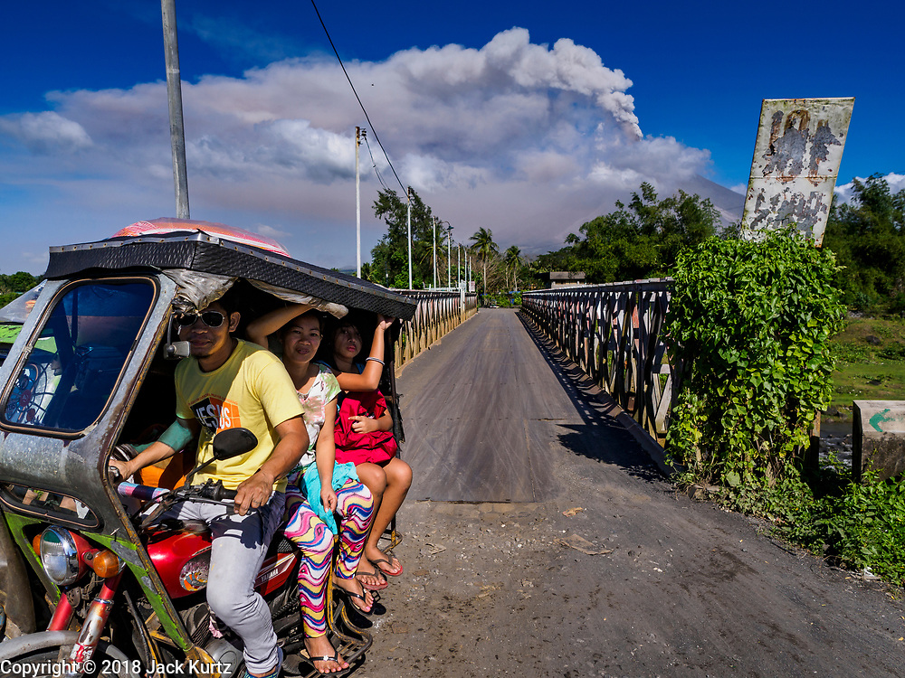 23 JANUARY 2018 - DARAGA, ALBAY, PHILIPPINES: People leave a community close to the Mayon volcano as smoke from an eruption builds over the volcano. The Mayon volcano continued to erupt Tuesday, although it was not as active as it was Monday. There were ash falls in communities near the volcano. This is the most active the volcano has been since 2009. Schools in the vicinity of the volcano have been closed and people living in areas affected by ash falls are encouraged to stay indoors, wear a mask and not participate in strenuous activities.    PHOTO BY JACK KURTZ