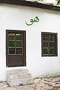 A black door and window against a white wall with a sign painted on the wall meaning Him (God) in Arab writing (spelled 'hu' as used by a certain religious sect.). The source of the Buna river and the house of the Whirling Dervishes, an old Muslim monastery, Blagaj. Federation Bosne i Hercegovine. Bosnia Herzegovina, Europe.