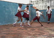 Students play Kick the Can on the rooftop playground of Rene Fraga Moreno Primary School  in Habana Vieja.