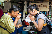 28 MARCH 2013 - BANGKOK, THAILAND:  Michelle Kao (RIGHT) thanks a woman who has a street food stall after the woman gave Michelle a bag of fruit.    PHOTO BY JACK KURTZ