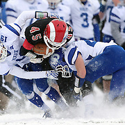 Morgan Carson, (centre), New Canaan Rams, is tackled by Griffin Ross, (left), Darien, during the New Canaan Rams Vs Darien Blue Wave, CIAC Football Championship Class L Final at Boyle Stadium, Stamford. The New Canaan Rams won the match in snowy conditions 44-12. Stamford,  Connecticut, USA. 14th December 2013. Photo Tim Clayton