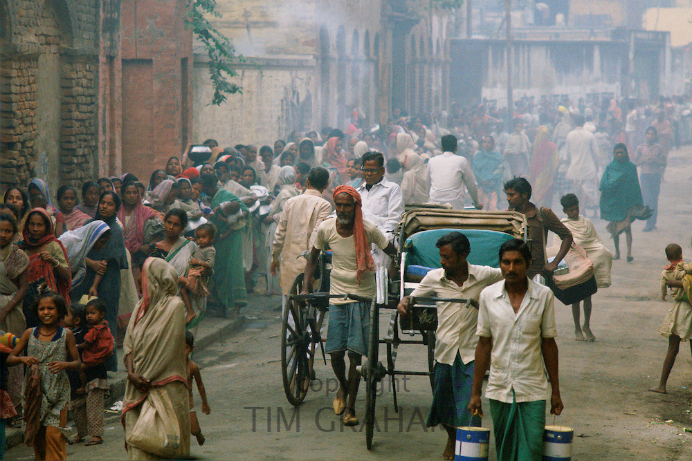 Rickshaws pass as poor people queue for food in the early morning at Mother Teresa's Mission in Calcutta, India.