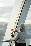 Woman in head scarf holding rose and taking a picture of London cityscape, London, England, UK