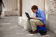 A photographer busily prepares his files on his Mac laptop to swiftly wire to his newpaper or wire service. Modern technology allows for photographs to be send from the field using mobile internet services.