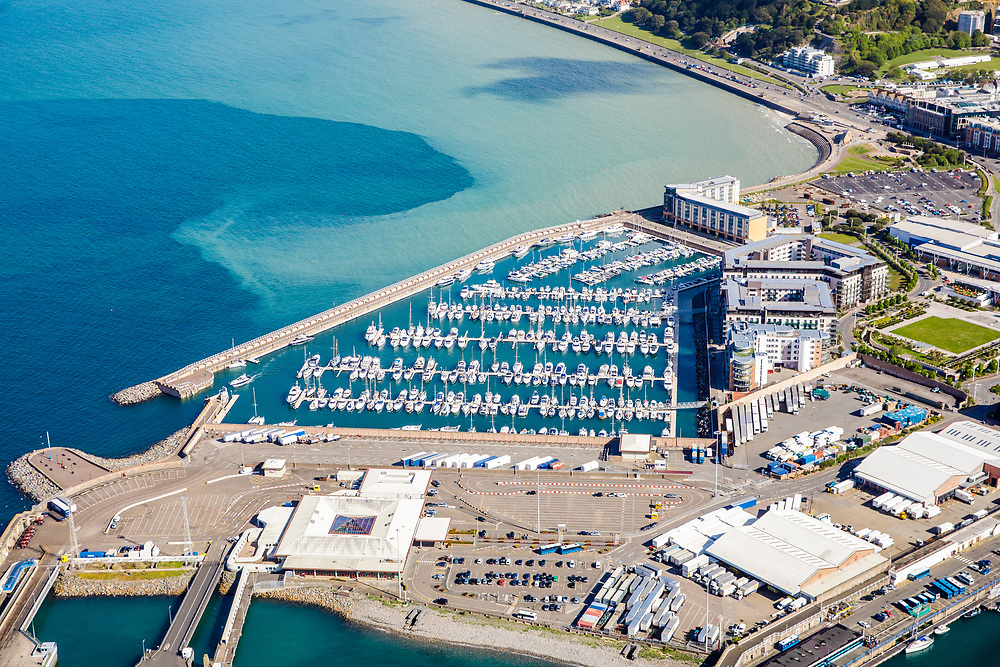 Aerial view of yachts and speedboats moored up at Jersey harbour, the waterfront and Catsle Quay apartments and flats.