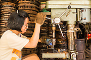 26 APRIL 2013 - BANGKOK, THAILAND:    A woman operates a drill press in a mechanical shop in a workshop in Talat Noi. The Talat Noi neighborhood in Bangkok started as a blacksmith's quarter. As cars and buses replaced horse and buggy, the blacksmiths became mechanics and now the area is lined with car mechanics' shops. It is one the last neighborhoods in Bangkok that still has some original shophouses and pre World War II architecture. It is also home to a  Teo Chew Chinese emigrant community.      PHOTO BY JACK KURTZ