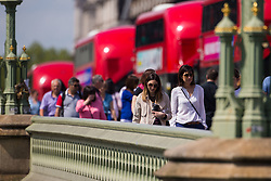 Red London buses queen's on Westminster Bridge as tourists enjoy the hot sunshine. London, May 09 2018.