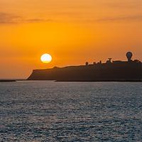 The sun sets behind Pillar Point Air Force Station & El Granada Harbor near Half Moon Bay, California.