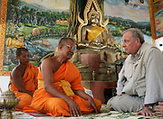 Canadian Prime Minister Paul Martin (R) listens to a monk recount the story of the Indian Ocean tsunami disaster near Kamala Beach in Phuket, Thailand, January 16, 2005.  Three monks from the temple died along with six Canadians, and 34 are still missing.  REUTERS/Jim Young