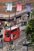 Seen from the elevation from the Marble Arch Mound, traffic and buses drive along Oxford Street where shoppers walk on the pavement, on 11th August 2021, in London, England.