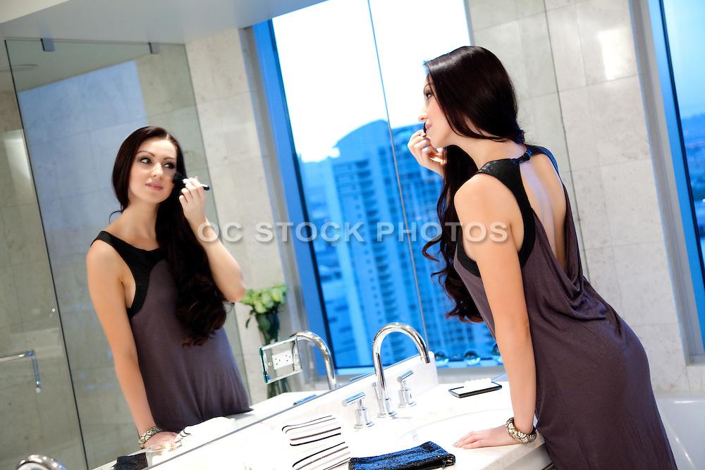 Pretty Brunette Applying Makeup In Bathroom