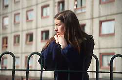 Teenage girl leaning against railings outside block of flats looking thoughtful,