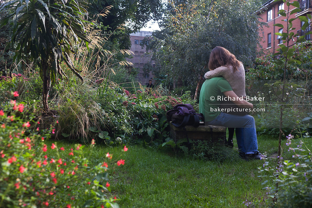 As two young lovers cuddle intimately in Phoenix Gardens, a voyeuristic stranger seemingly looks through bushes.