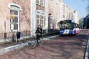 Een vrouw fietst door het centrum van Utrecht. Achter haar rijdt de Museumlijn.<br /> <br /> A woman is cycling in Utrecht