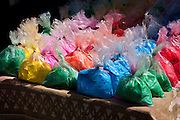 Bags of powder colours for traditional Hindu Holi festival on sale at market stall in old town Udaipur, Rajasthan, Western India