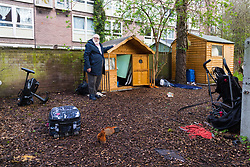 Danny Gallivan, chairman of the Regent's Park Gardening Association stands by a small wooden wendy house in a section of an allotment reserved as a children's play area appears to have become the residence or storage shed of  homeless individuals, said by one local resident to be Romanian beggars who sleep in a lane behind the nearby tower blocks. Munster Square, Camden, March 18 2019.