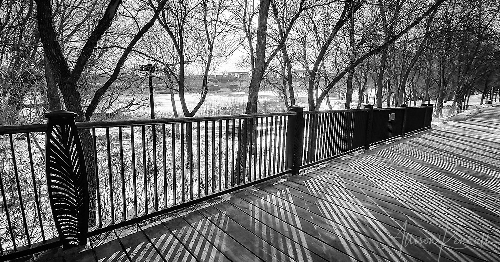 Winter light through ornamental railings along a path in Stephen Juba park overlooking the Red River in downtown Winnipeg, Manitoba