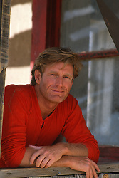 Good looking man in a red shirt leaning on a wooden window frame