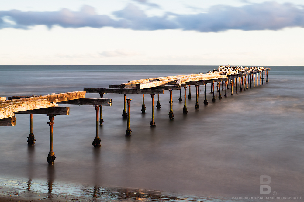 An old pier sits out on the Strait of Magellen in Punta Arenas, Chile.