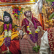 A young boy dressed and the Indian God Shiva, and a girl dressed as his wife, Parvati, on a carriage during the Ramlila procession in Old Delhi, September 2009