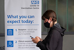 © Licensed to London News Pictures. 07/08/2021. London, UK. A woman braves the heavy rain weather queuing outside the ARSENAL EMIRATES STADIUM to attend the second mass Covid 19 vaccination event. Photo credit: Ray Tang/LNP