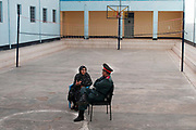 Afghanistan. Herat Women's prison. Prison governor with woman prisoner, having a conversation on the basketball court