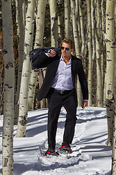 hot man in a suit walking through the snow in snowshoes