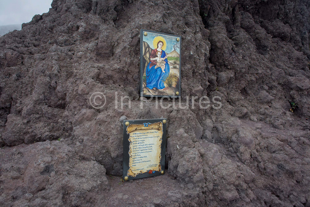 Religious shrine and old lava on the crater edge of Vesuvius volcano, Italy. The Madonna is seen holding a baby Jesus with a smoking volcano in the background. Hardened lava rock has formed a new crust o the crater edge where visitors can view over to see the bottom of the abyss. Mount Vesuvius is best known for its eruption in AD 79 that led to the burying and destruction of the Roman cities of Pompeii and Herculaneum. That eruption ejected a cloud of stones, ash and fumes to a height of 33 km (20.5 mi), spewing molten rock and pulverized pumice at the rate of 1.5 million tons per second. From the chapter entitled 'Under the Volcano' and from the book 'Risk Wise: Nine Everyday Adventures' by Polly Morland (Allianz, The School of Life, Profile Books, 2015).