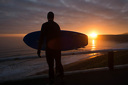 © Licensed to London News Pictures. <br /> 05/04/2015. <br /> <br /> Saltburn, United Kingdom<br /> <br /> A surfer stands and watches the sunrise before heading out for a morning surf on Easter Sunday in Saltburn, United Kingdom.<br /> <br /> Photo credit : Ian Forsyth/LNP