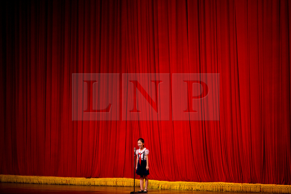 © Licensed to London News Pictures. 11/08/2011. Pyongyang, North Korea. A young girl introduces a performance at the Mangyongdae Children's Palace in Pyongyang to an audience of parents, party officials, and tourists.  The children's palace is a centre where the country's most academic and athletic students come to perfect their skills. Photo credit : James Gourley/LNP/