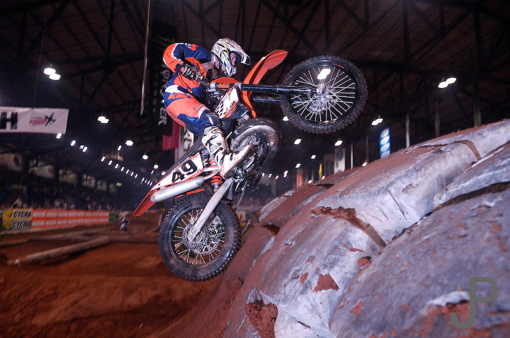 Stillwater, Oklahoma native Guy Cooper #49 launching his KTM over the tire obstacle at the 2007 Maxxis AMA Endurocross at the Lazy E Arena in Guthrie, Oklahoma.  Event was won by David Knight #101 on KTM