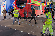 Workman carry a construction fence past shoppers while crossing Oxford Street, central London.