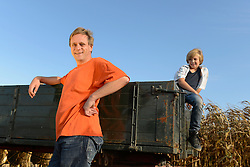 Father and son standing by tractor, Bavaria, Germany