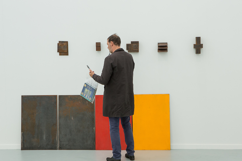 New York, NY - 6 May 2016. Frieze New York art fair. A man checks his phone in one of the gallery exhibits.