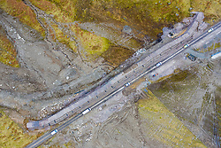 Glen Croe, Arrochar, Scotland, UK. 22 Feb 2021. Aerial view of landslide preventative engineering works to A83 at rest and be Thankful Pass in Glen Croe. The important route has been plagued by landslips which have often closed the main A83 carriageway forcing traffic to use single track Old Military road below. Latest landslides have  even blocked this road. Currently traffic is escorted one way in convoys. Pic; Convoy on Old Military road at new wall.   Iain Masterton/Alamy Live News