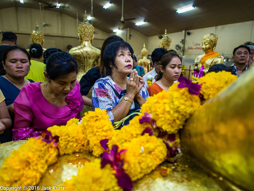 14 JANUARY 2016 - CHACHOENGSAO, CHACHOENGSAO, THAILAND: People pray at the feet of a statue of the Buddha at Wat Sothon. Wat Sothon, in Chachoengsao, is one of the largest Buddhist temples in Thailand. Thousands of people come to the temple every day to pray for good luck, they make merit by donating cooked eggs and cash to the temple. The temple dates from the Ayutthaya period (circa 18th century CE).         PHOTO BY JACK KURTZ