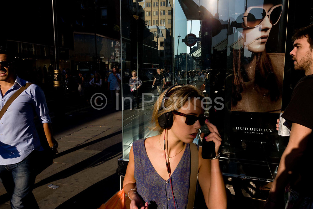 A young woman listens to mp3 music beneath a poster girl for Burberry sunglasses they call Eyewear, in a sunlit London street. Burberry Group plc is a British luxury fashion house, manufacturing clothing, fragrance, and fashion accessories.
