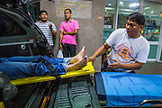 """30 NOVEMBER 2012 - BANGKOK, THAILAND: Volunteer medics with the Ruamkatanyu Foundation unload a woman who collapsed on a Bangkok street from their ambulance at Police General Hospital in Bangkok during a Friday night shift. The Ruamkatanyu Foundation was started more than 60 years ago as a charitable organisation that collected the dead and transported them to the nearest facility. Crews sometimes found that the person they had been called to collect wasn't dead, and they were called upon to provide emergency medical care. That's how the foundation medical and rescue service was started. The foundation has 7,000 volunteers nationwide and along with the larger Poh Teck Tung Foundation, is one of the two largest rescue services in the country. The volunteer crews were once dubbed Bangkok's """"Body Snatchers"""" but they do much more than that now.     PHOTO BY JACK KURTZ"""